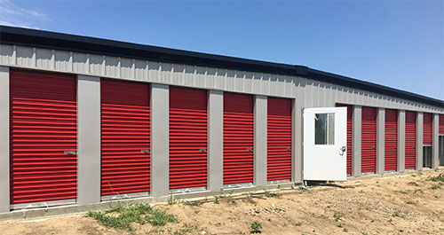outdoor single-story, metal storage facility with red doors.